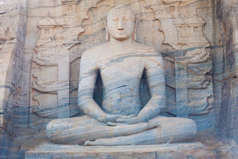 条纹的坐的菩萨雕象Polonnaruwa前面 库存照片