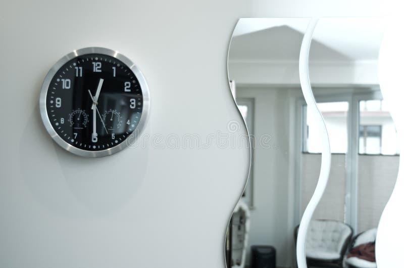 来回黑色壁钟和镜子 图库摄影