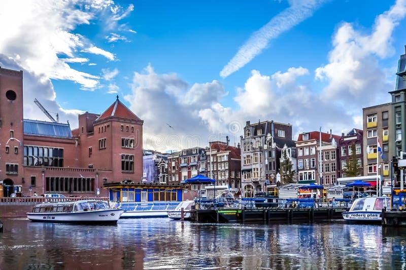 来来往往从Damrak运河的旅游运河船在阿姆斯特丹的老市中心 库存图片