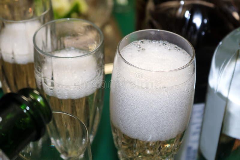 来的泡影在一块泡沫似的玻璃的倒的香槟与周围的瓶形状和倾吐的更多香槟 免版税库存图片