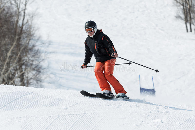 来自下来滑雪山的少妇滑雪者在晴天 库存照片