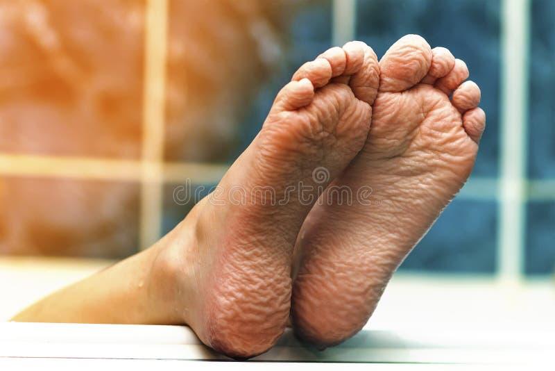 来自浴缸的起皱纹的赤脚 年轻人getti 免版税库存图片