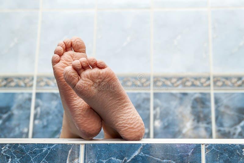 来自浴缸的起皱纹的赤脚 年轻人getti 库存图片
