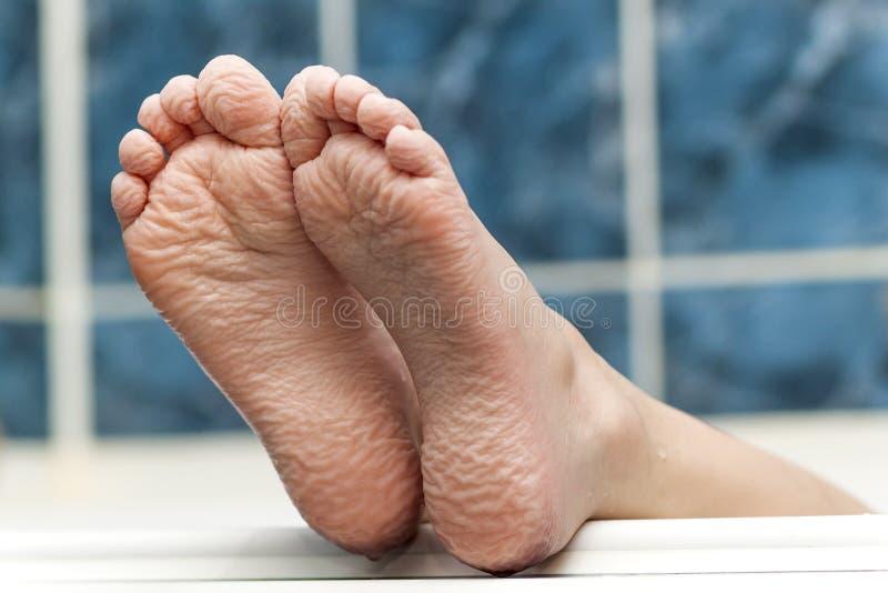 来自浴缸的起皱纹的赤脚 年轻人getti 库存照片