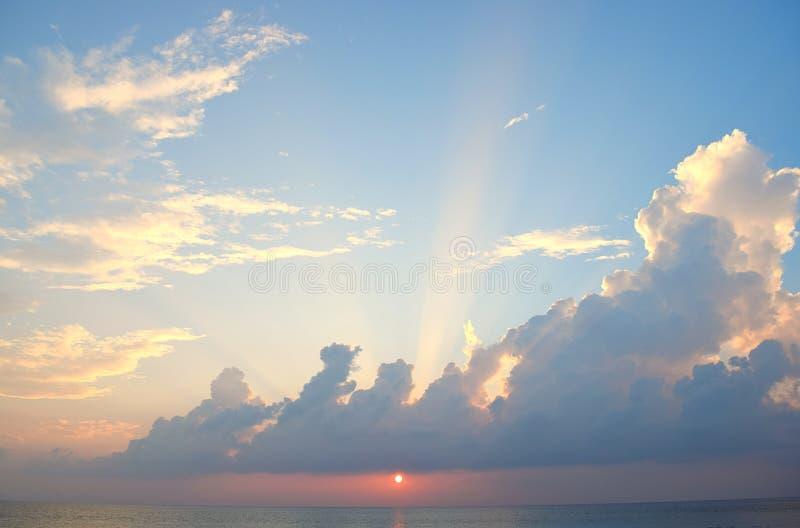 来通过在天空蔚蓝的云彩的明亮的阳光与在海洋的金黄太阳设置 图库摄影