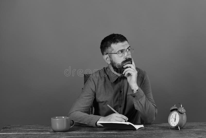 杯、减速火箭的时钟和红色书在葡萄酒桌上 有想法的面孔的人坐在木桌上 免版税图库摄影