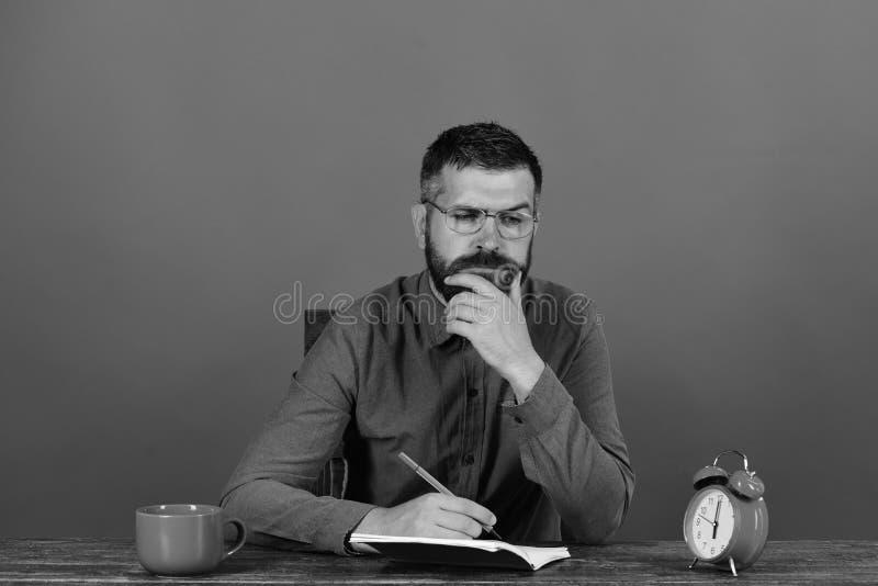 杯、减速火箭的时钟和红色书在葡萄酒桌上 有胡子的,玻璃人在笔记本写在红色背景 免版税图库摄影