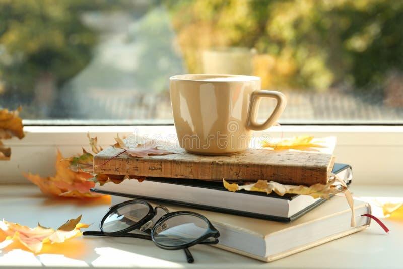 杯与书和秋叶的热的咖啡在窗台 免版税库存照片