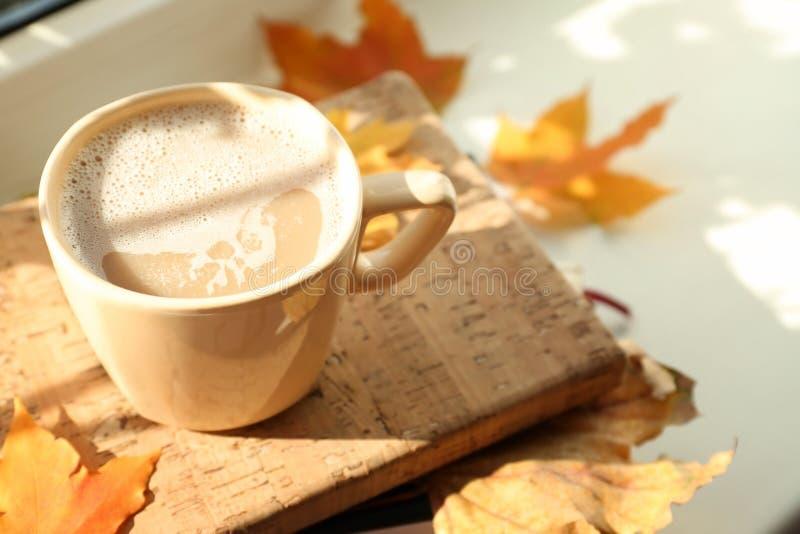 杯与书的热的咖啡和在窗台,特写镜头的秋叶 免版税库存图片