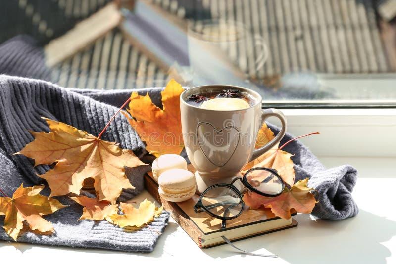 杯与书的芳香茶,温暖的毛线衣和秋叶在窗台 免版税库存图片