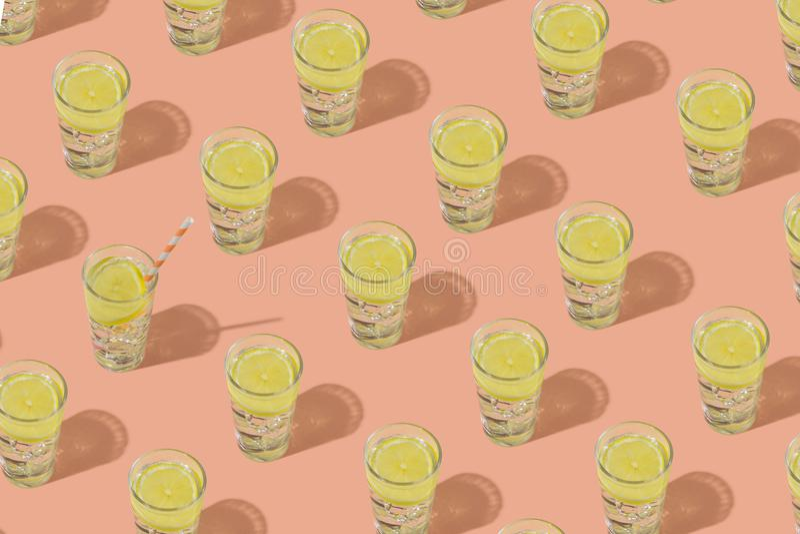 杯与冰和柠檬的凉水 重复在桃红色背景的样式 免版税库存照片