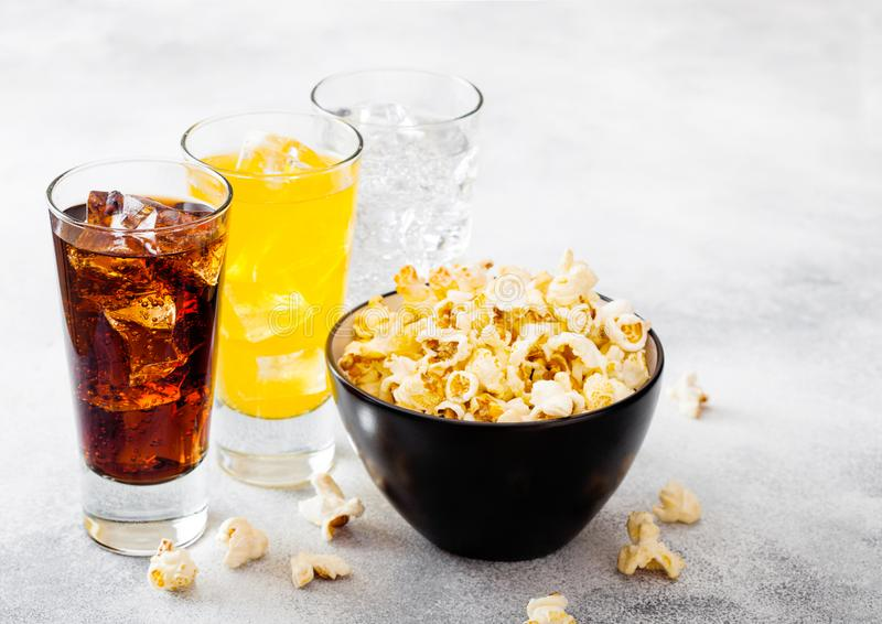 杯与冰块和黑碗的苏打饮料在石厨房用桌背景的玉米花快餐 可乐和橙色和清楚 免版税图库摄影