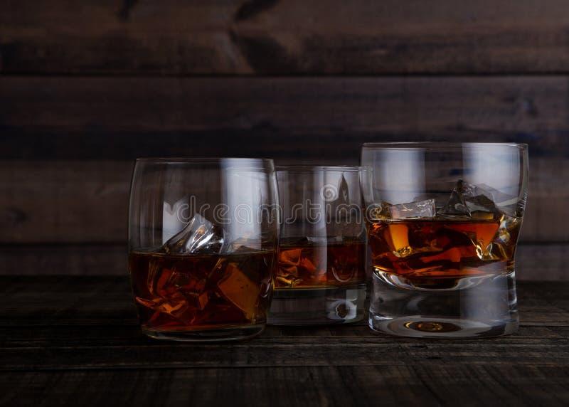 杯与冰块的威士忌酒在木桌上 库存图片