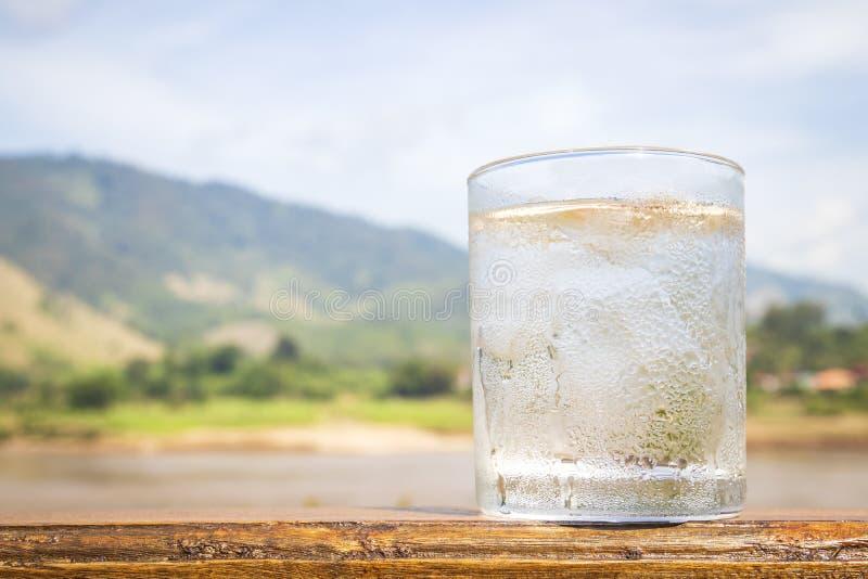 杯与冰块的水在木桌上有山和天空背景 免版税库存图片