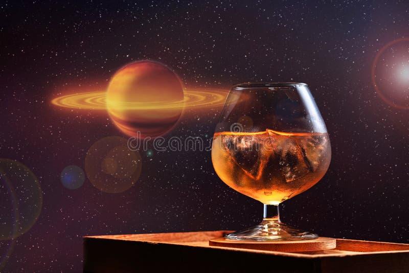 杯与冰的威士忌酒在星宇宙天空和一个黄色红色行星的背景 图库摄影