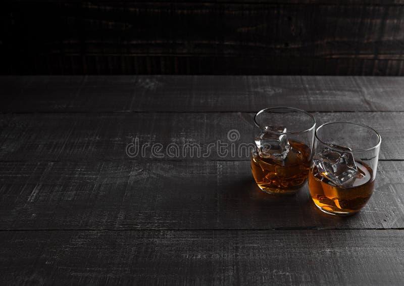 杯与冰的威士忌酒在木背景 免版税库存照片