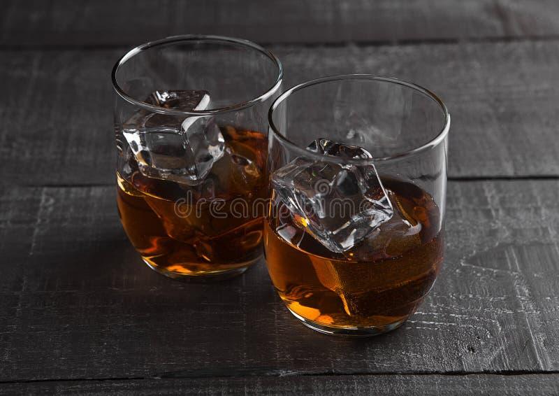 杯与冰的威士忌酒在木背景 免版税库存图片