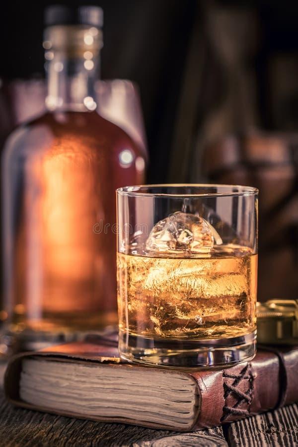 杯与冰的威士忌酒在老学报 库存照片