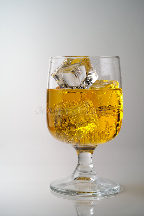 杯与冰的黄色饮料 免版税库存图片