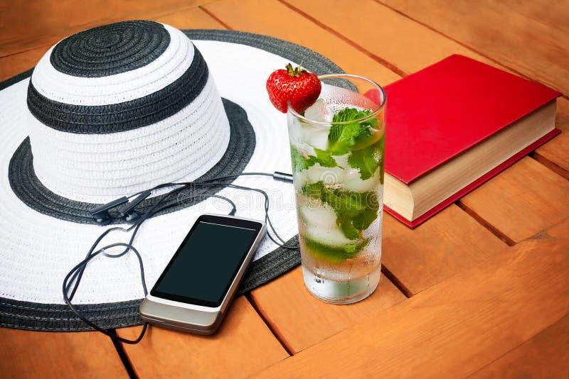 杯与冰的水和薄菏、夏天帽子、书和智能手机 图库摄影