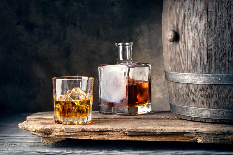 杯与冰蒸馏瓶和桶的威士忌酒 库存照片