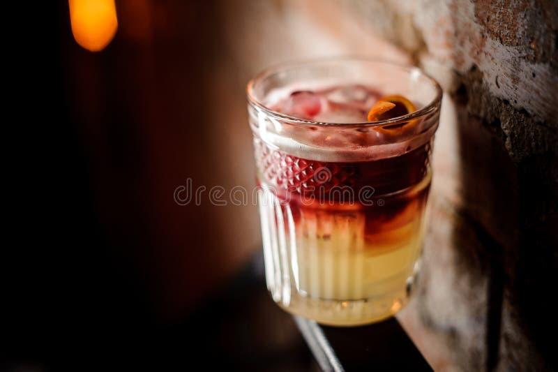 杯与切片的红色和白色酒精鸡尾酒橙皮 免版税库存照片