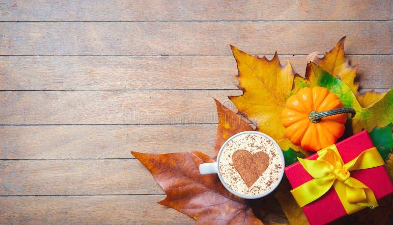 杯与心脏形状的热奶咖啡和在槭树的礼物盒离开 免版税库存照片