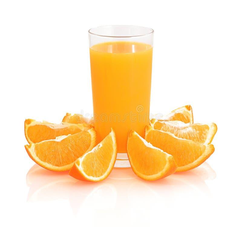 杯与新发光的橙色切片的橙汁在与阴影反射的白色背景隔绝的玻璃附近 免版税库存照片
