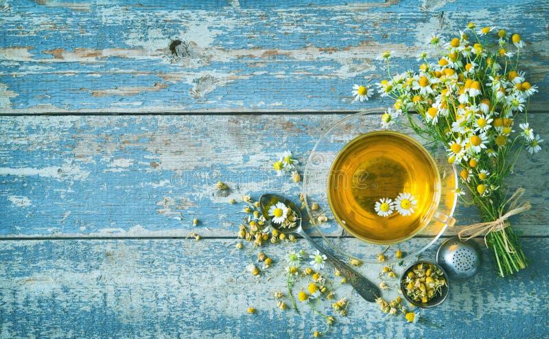 杯与春黄菊花的清凉茶在年迈的蓝色木板条 免版税图库摄影