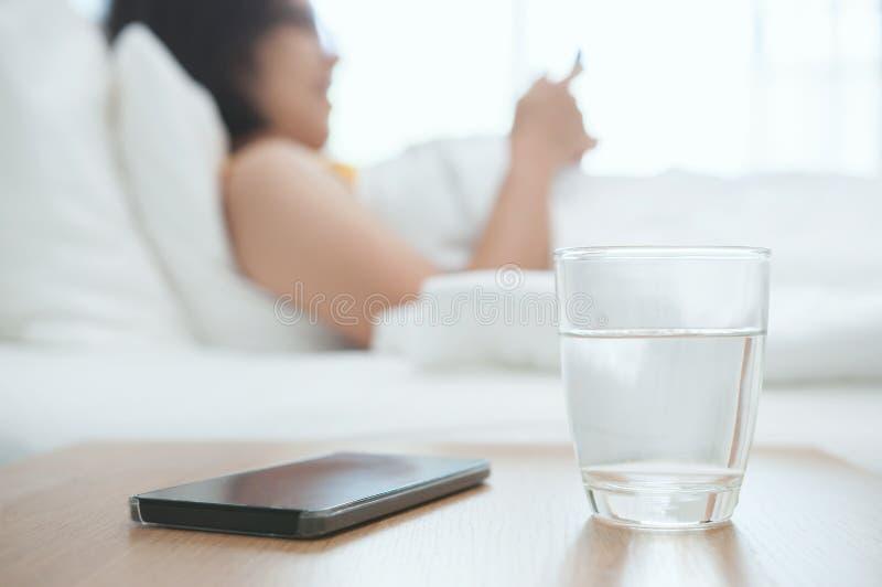 杯与智能手机的水 库存照片