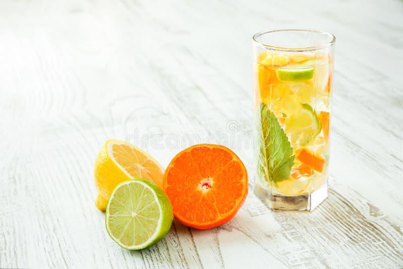 杯与柠檬、石灰和蜜桔切片、薄荷叶和被击碎的冰的新和健康夏天饮料在白色木桌上 免版税库存照片