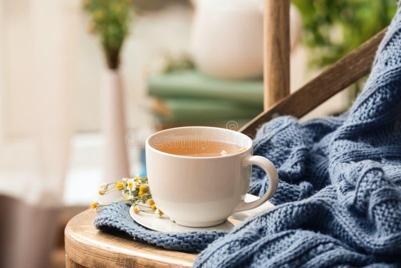 杯与格子花呢披肩的可口甘菊茶在椅子 库存照片