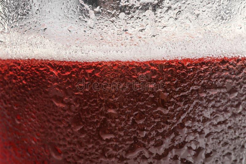 杯与泡沫特写镜头的鲜美红色啤酒 免版税库存图片
