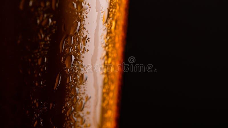 杯与泡沫的啤酒在黑背景特写镜头 免版税库存照片