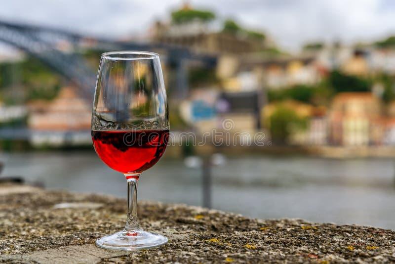 杯与波尔图葡萄牙被弄脏的都市风景的葡萄酒在背景中 免版税库存图片
