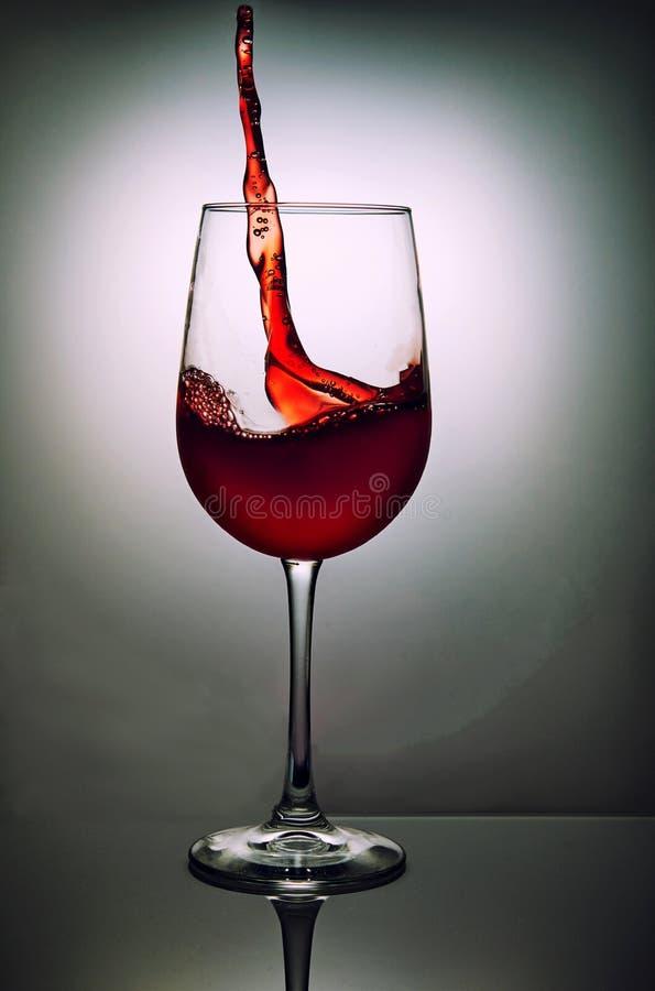 杯与波浪的红酒在灰色背景 免版税库存图片