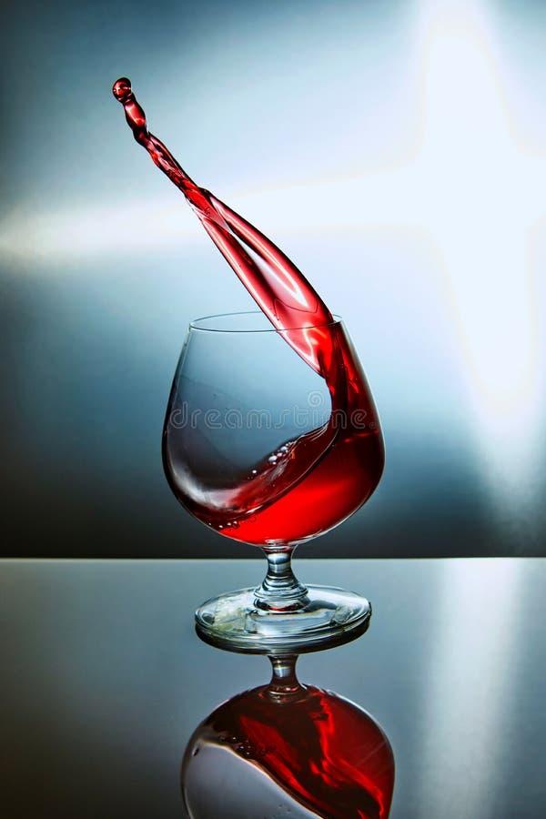 杯与波浪的红酒在蓝色背景 免版税库存照片