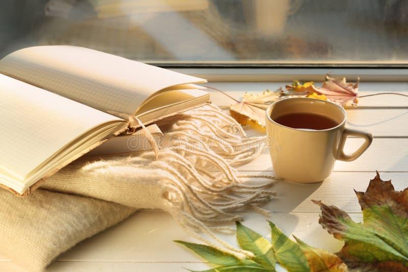 杯与温暖的格子花呢披肩、笔记本和秋叶的芳香茶在白色木窗台 免版税库存图片