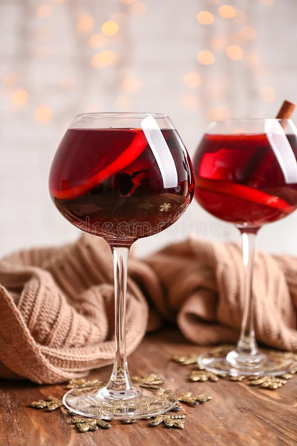 杯与温暖的格子花呢披肩的可口加香料的热葡萄酒在木桌上 库存照片
