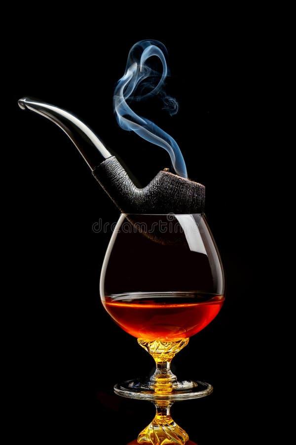 杯与烟斗的科涅克白兰地 库存照片