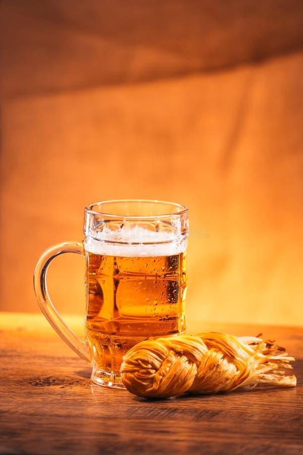 杯与熏制的乳酪辫子的新鲜的明亮的啤酒在袋装 免版税图库摄影