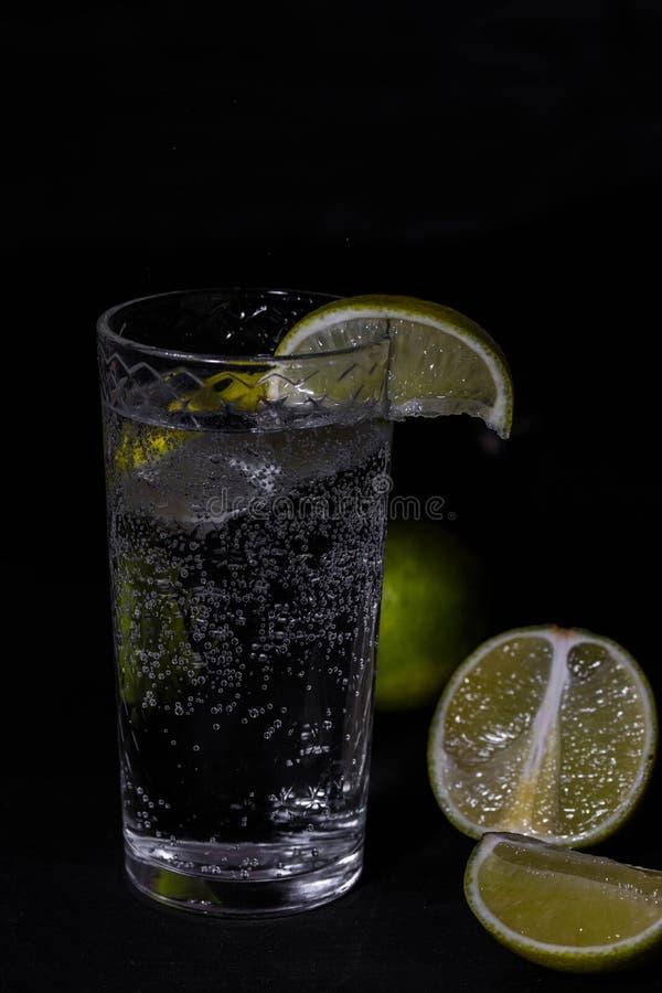 杯与石灰的苏打在黑暗的摄影样式 库存照片