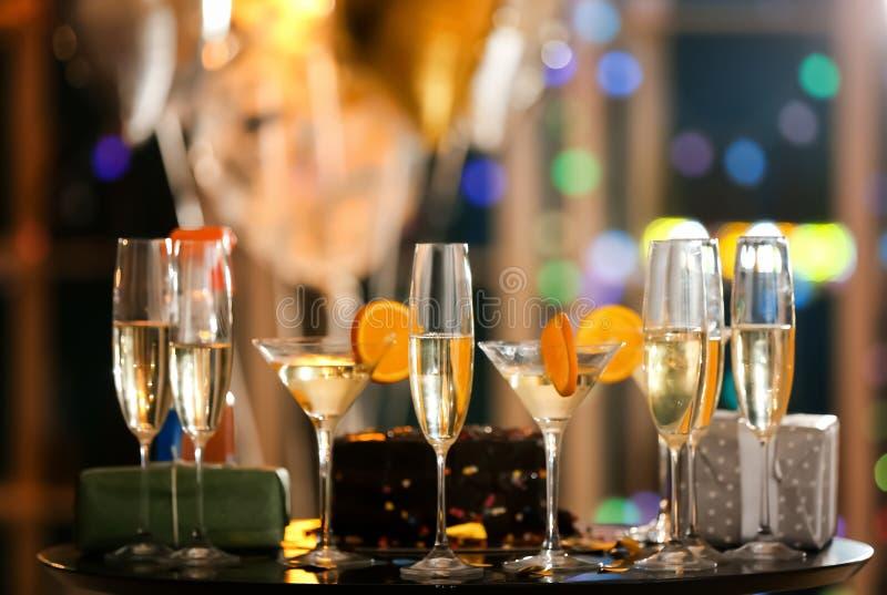 杯与礼物盒的酒精在生日宴会的桌上俱乐部的 库存照片