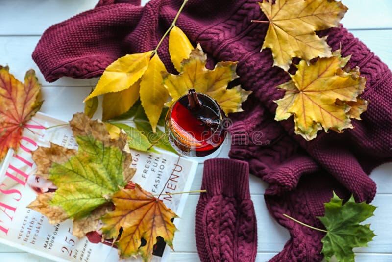 杯与秋叶、杂志和温暖的毛线衣的可口加香料的热葡萄酒在白色木桌上 库存照片