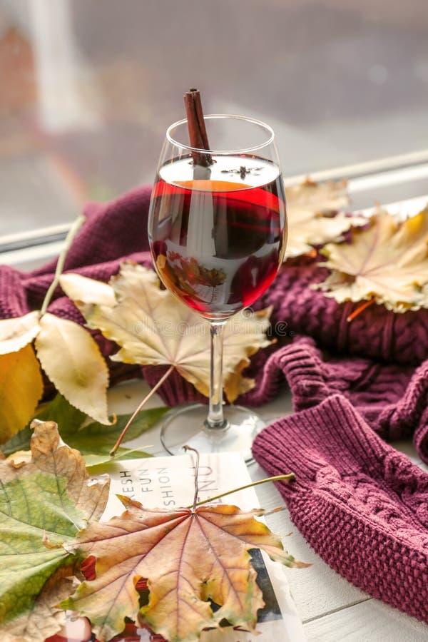 杯与秋叶的可口加香料的热葡萄酒和在木窗台的温暖的毛线衣 库存照片