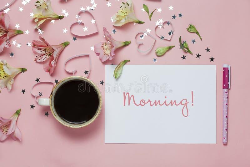 杯与笔的coffe和春天问候,花构成和词早晨在桃红色背景 顶视图,平的位置 免版税库存图片