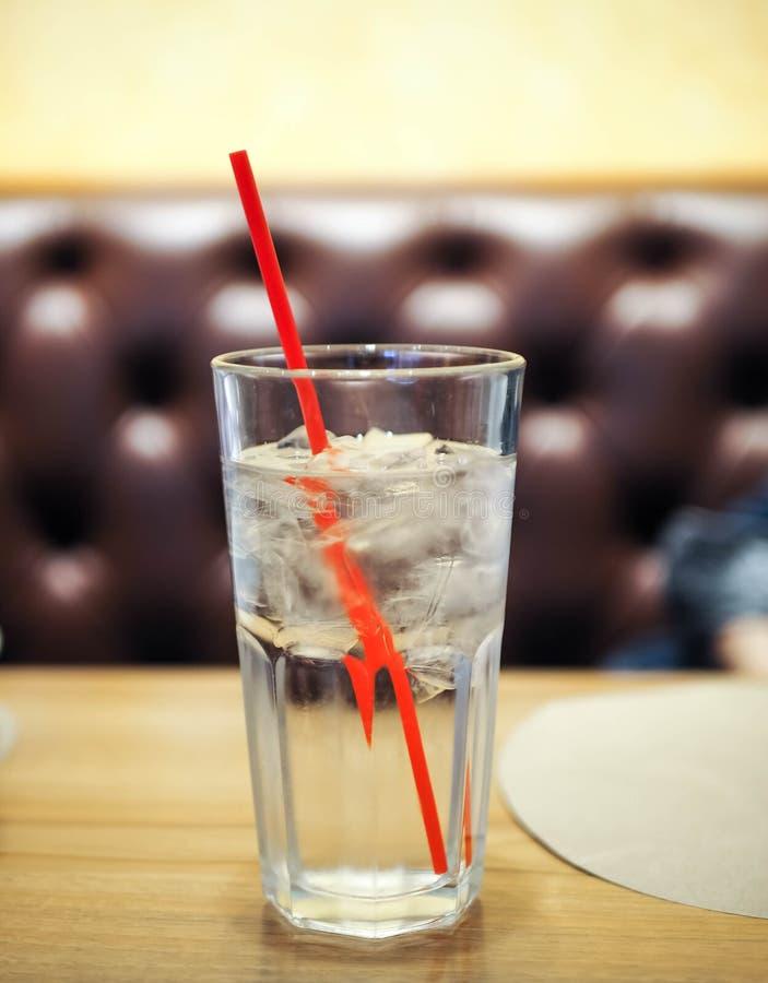 杯与红色秸杆的水在木桌上 免版税库存图片