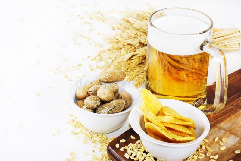 杯与芯片和花生的冰镇啤酒在白色背景 免版税库存照片