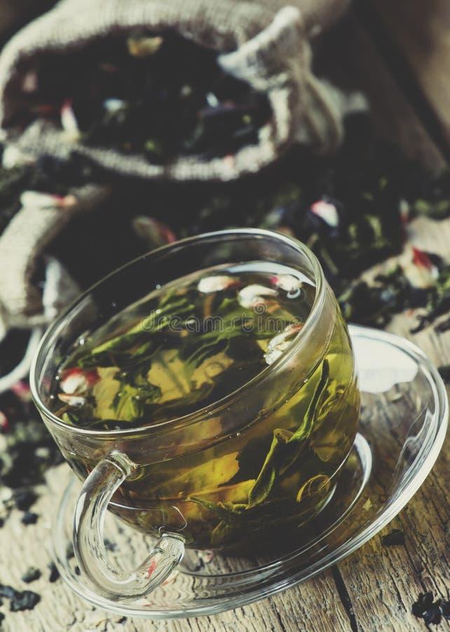 杯与花瓣和果子,葡萄酒木b的绿茶 免版税库存图片