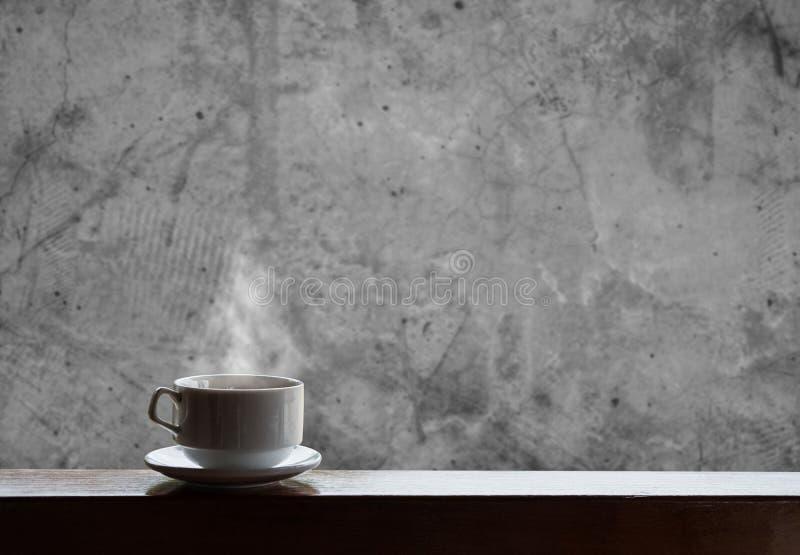杯与蒸汽的热的饮料在木桌上和具体背景、热的咖啡、茶、巧克力和等 免版税库存图片